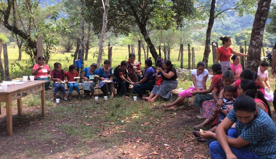 women community leaders of Ixquisis gather together beneath large trees.