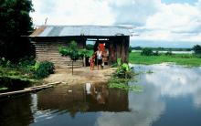 family outside home in Colombia, surrounded by water