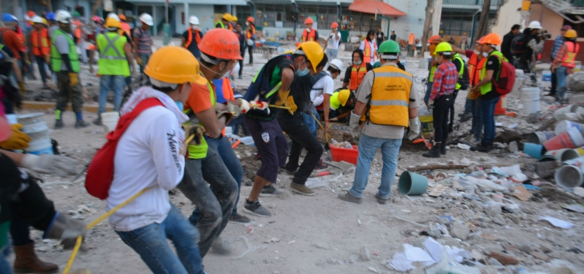 human chain in the ruins of a building destroyed by an earthquake
