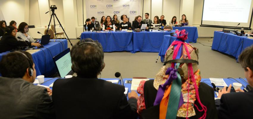 people seated in long tables before giving testimony before the IACHR